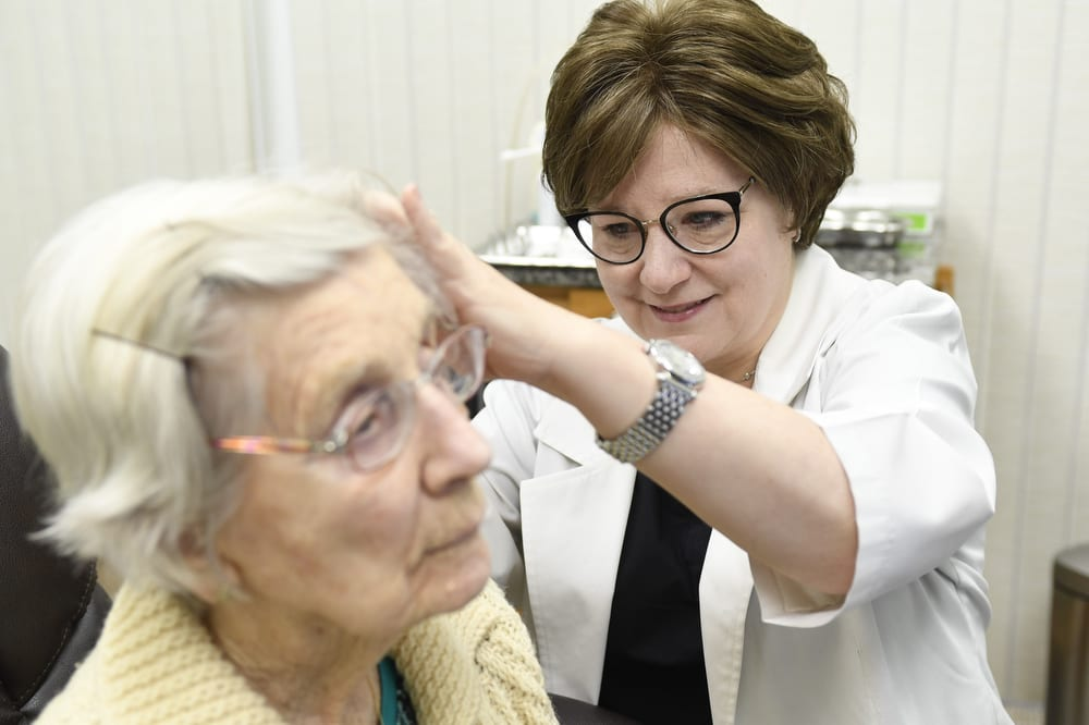 elderly woman having her hearing assessed
