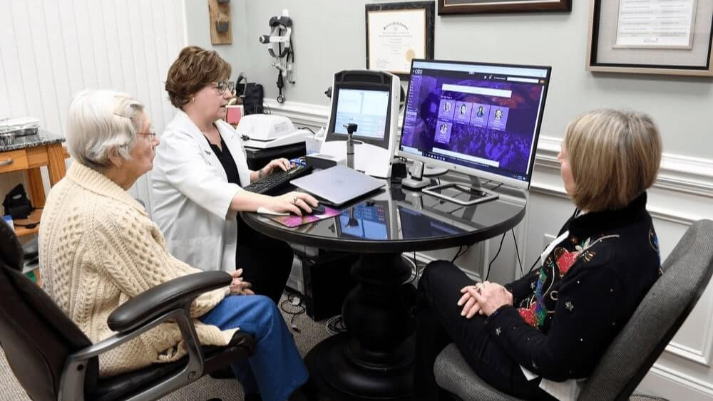 Audiologist with senior patient and her family member